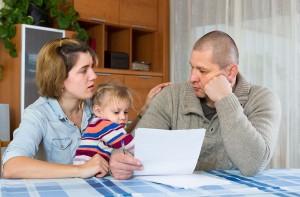 Des parents lisant leurs factures avec leur enfant via Shutterstock