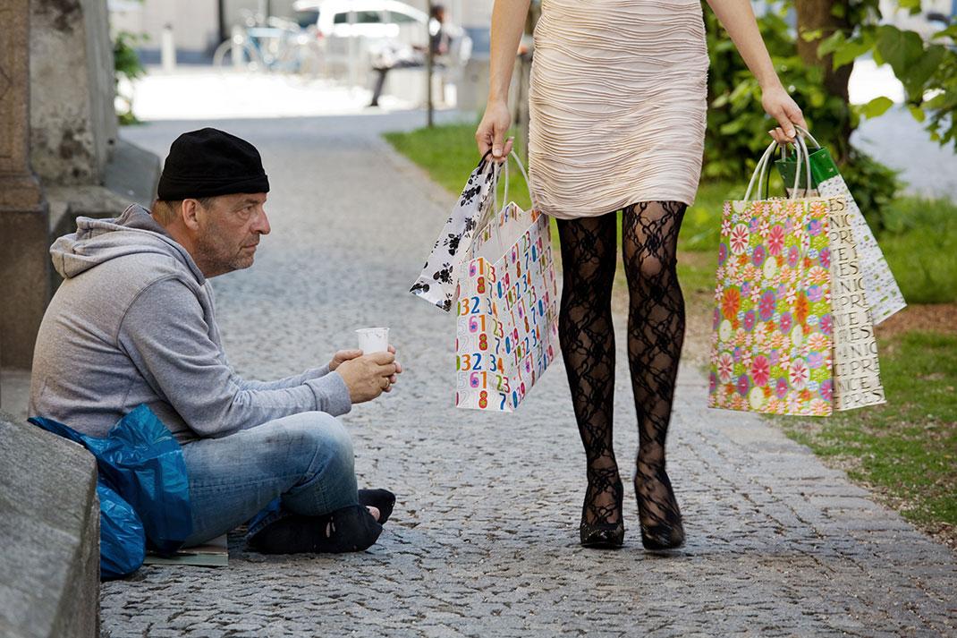 Un mendiant à côté d'une femme portant plusieurs sacs de shopping via Shutterstock