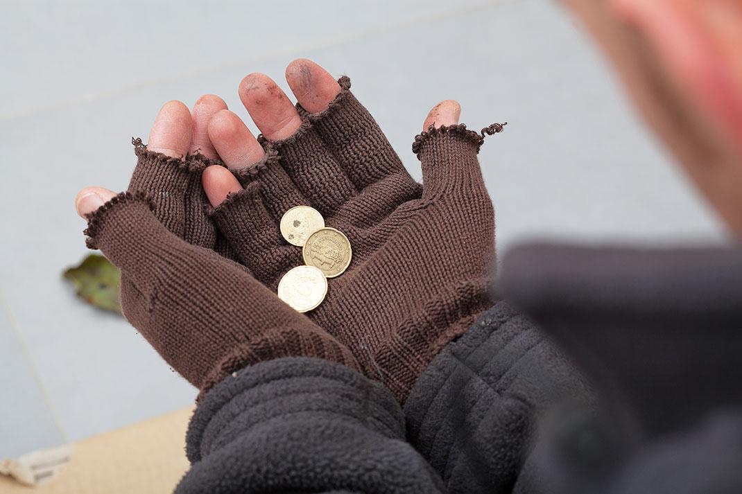 Un sans-abri avec des pièces dans ses mains gantées via Shutterstock