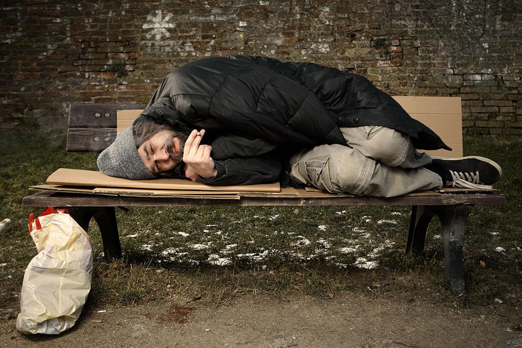 Un sans-abri dormant sur le banc d'un parc via Shutterstock