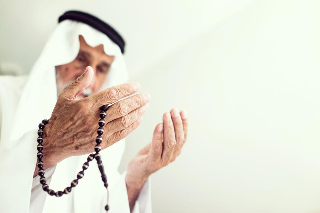 Un homme âgé effectue une prière via Shutterstock