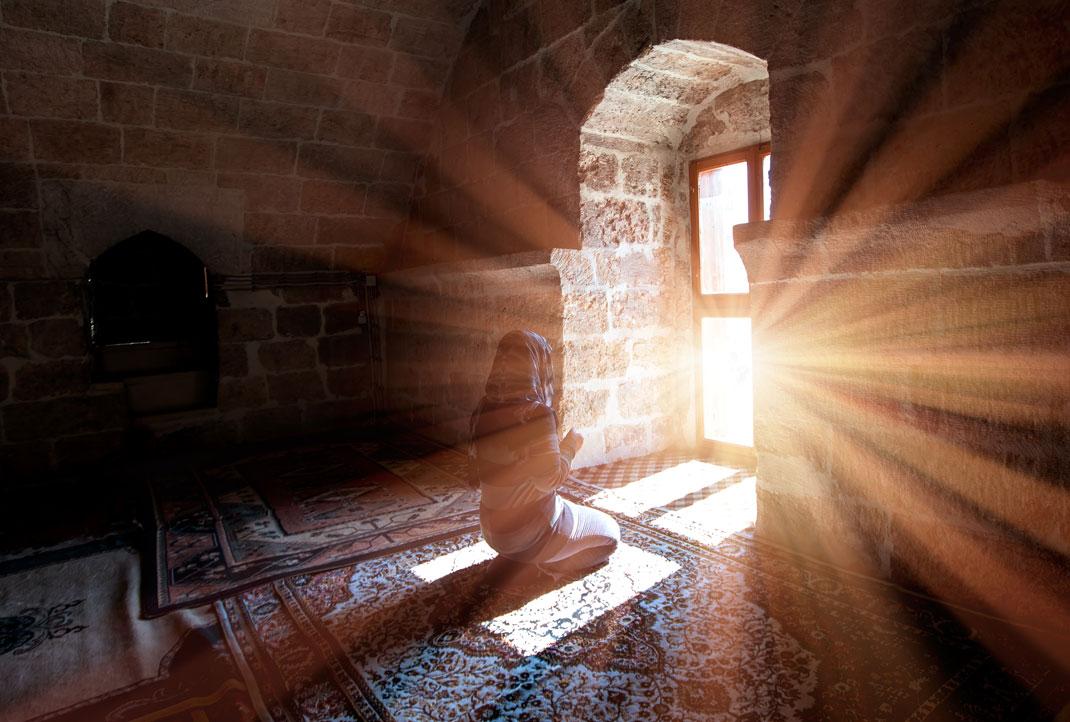 Une jeune musulmane faisant la prière via Shutterstock