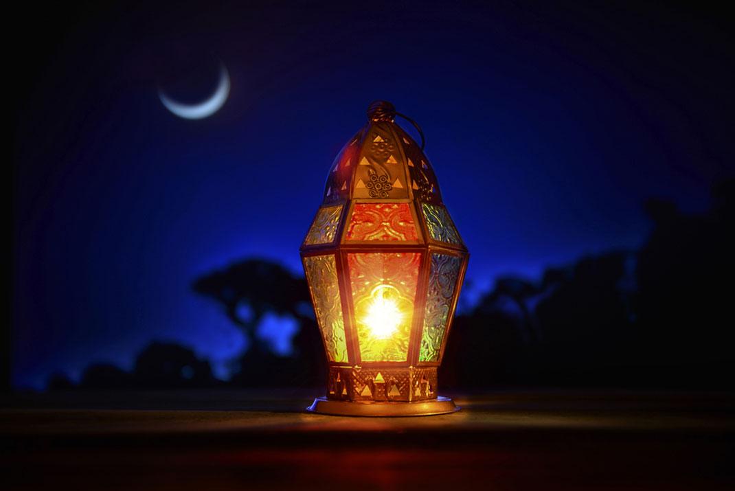 Une lanterne éclairée dans la nuit sombre via Shutterstock