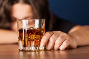 Une jeune femme avec un verre d'alcool à la main via Shutterstock
