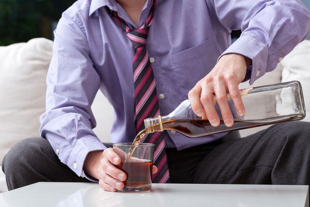 Un homme buvant de l'alcool seul via Shutterstock