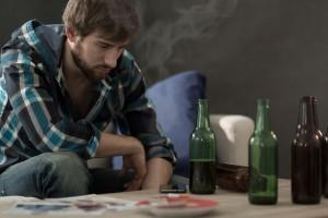 Un jeune homme buvant seul via Shutterstock