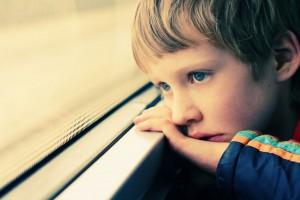 Un enfant regardant par la fenêtre via Shutterstock