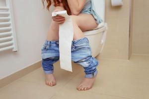 Une femme urinant aux toilettes via Shutterstock