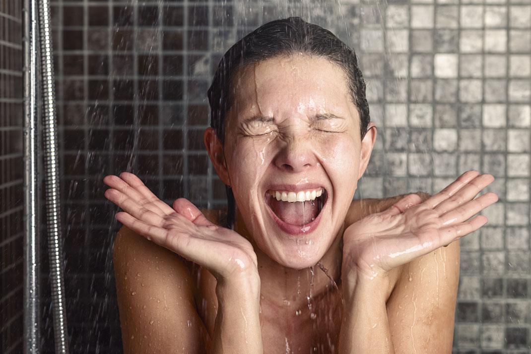 Une jeune femme sous la douche via Shutterstock