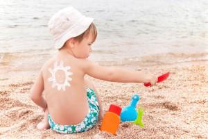 Un enfant sur la plage avec de la crème solaire via Shutterstock