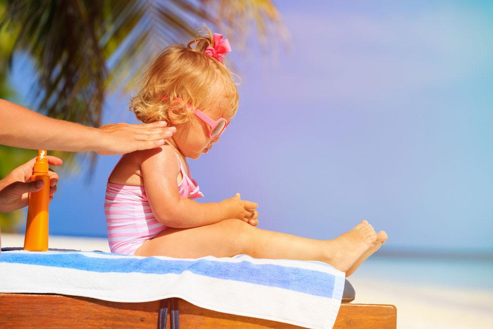 Une maman étant de la crème solaire sur son enfant via Shutterstock