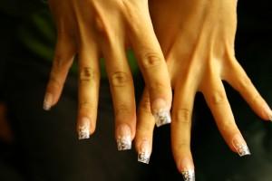 Des mains serties de faux ongles