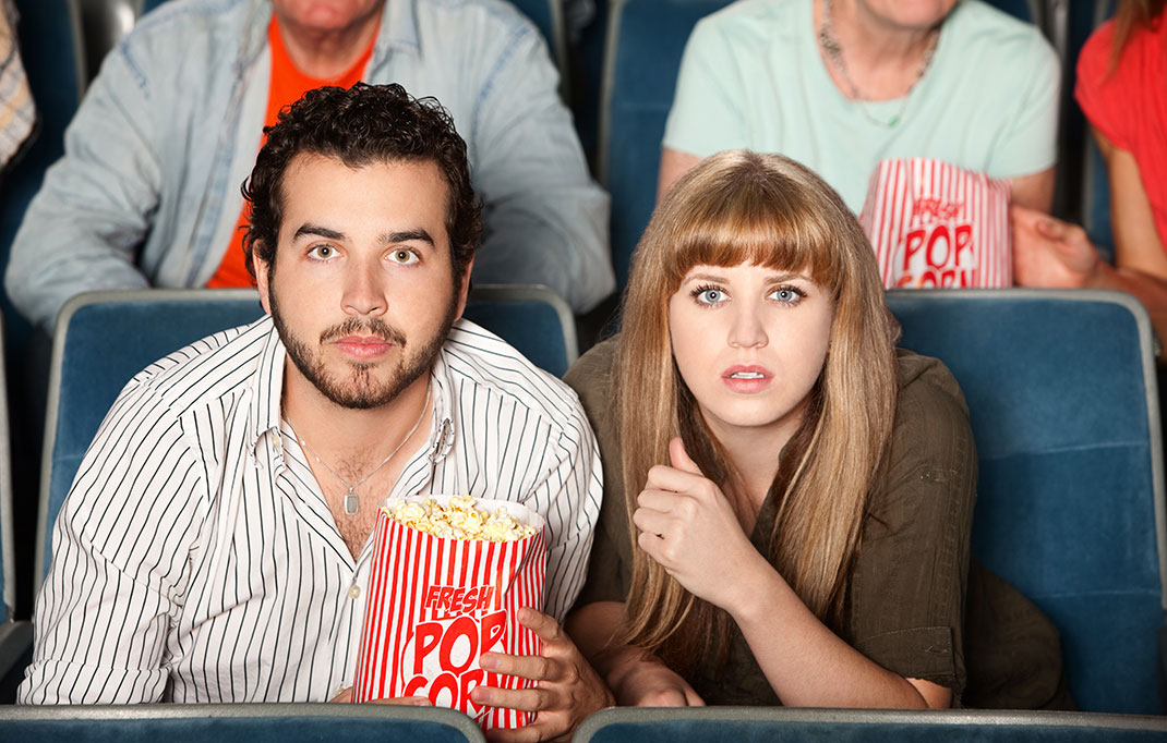 Un couple mange du popcorn au cinéma via Shutterstock