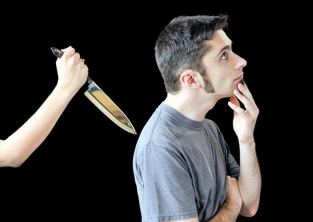 Un homme sur le point de se faire poignarder dans le dos via Shutterstock