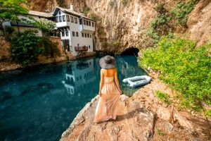 Une femme se tient face au Vrelo Bune en Bosnie via Shutterstock