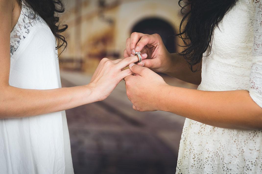 Une femme passe la bague au doigt de son épouse via Shutterstock