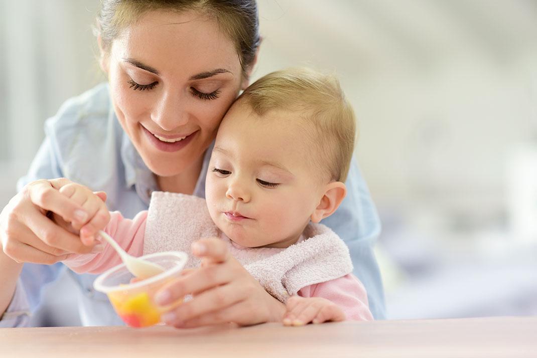Un bébé mange dans les bras de sa maman via Shutterstock