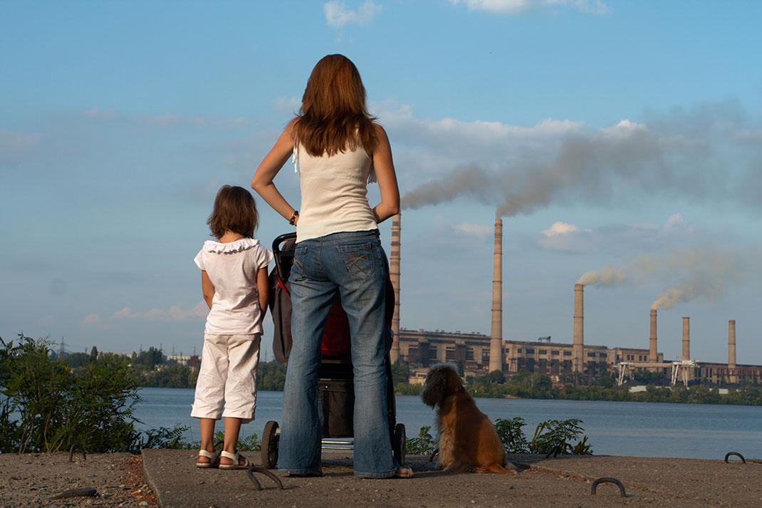 Une mère et ses enfants observent des cheminées polluant l'air via Shutterstock