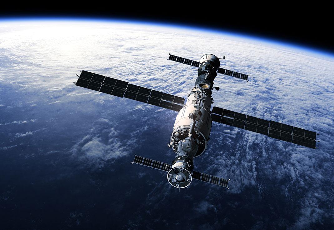Une station spatiale vole en orbite autour de la Terre via Shutterstock